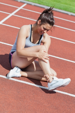 run down: Female runner with ankle injury on track