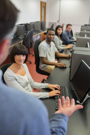 Teacher talking to the students at the university in computer class photo
