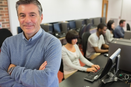 male teacher: Teacher smiling at top of computer class in college