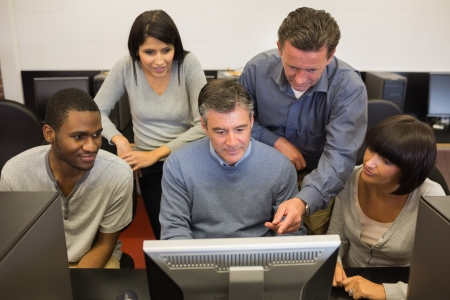 Mature students looking at computer in computer class in college Stock Photo - 18124833