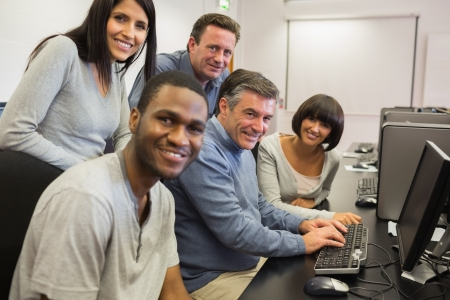 Teacher and students sitting at the computer and smiling  in computer class photo