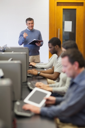 lecturing: Teacher talking to his computer class holding a clipboard in college Stock Photo