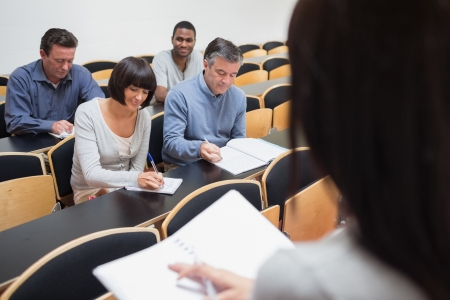Mature students taking notes in class at college photo