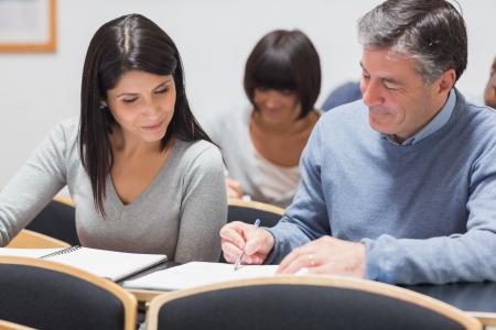Man toont vrouw iets op notitieblok in lezing op de universiteit en lachend Stockfoto