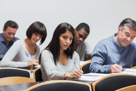 Mature students taking notes in lecture in college Stock Photo