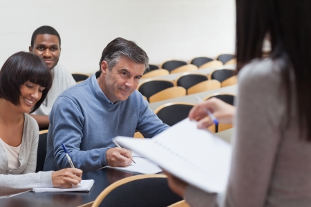 Mature students smiling and taking notes in lecture in college photo