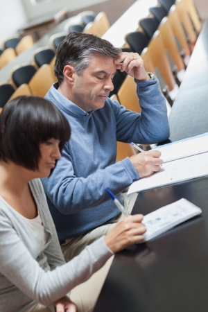 Mature students taking notes during lecture in lecture hall in college photo
