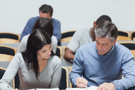 Man explaining to woman something on notepad in lecture hall in college photo