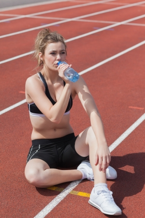 Blonde woman sitting on runing track and drinking bottled water photo
