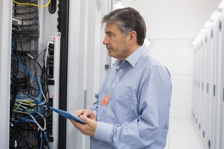 Man using tablet computer for maintenance on servers in data center photo