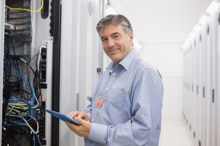 Smiling man doing maintenance on servers with tablet pc photo