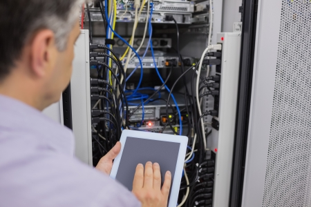 hardware repair: Man doing server maintenance with tablet pc in data center