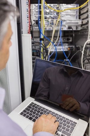 Man sitting with a laptop in front of a server and doing maintenance photo