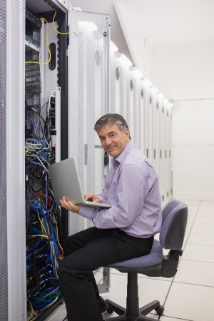 Smiling man working on laptop to check servers in data center photo