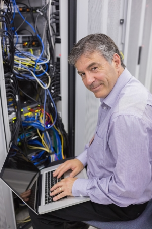 Man typing on laptop while doing server maintenance in data center and smiling photo