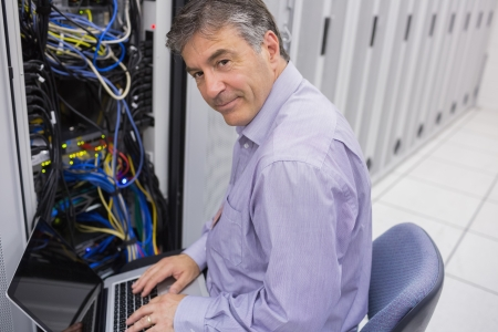 Man doing server  maintenance with notebook in data center and smiling photo