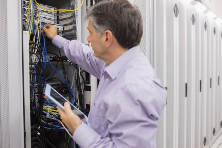 Man doing server maintenance with tablet pc in hallway of data center photo