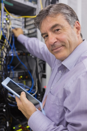technicians: Man smiling while doing server maintenance with tablet in hallway