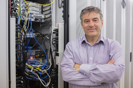 Smiling technician with arms crossed in front of server in data center photo