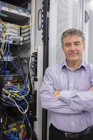 Smiling technician standing beside server with folded arms in data center photo