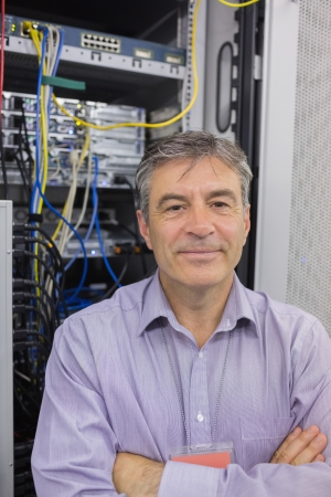 Smiling technician with crossed arms standing in front of servers in data center photo