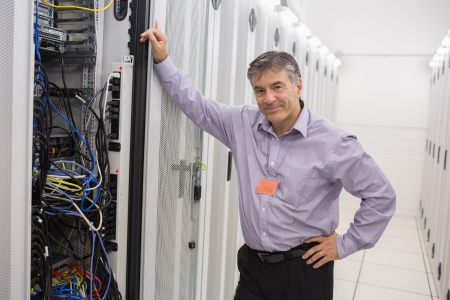 Smiling technician leaning against server in data center photo