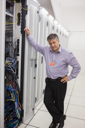 Man leaning on a server tower in hallway of data center and smiling photo