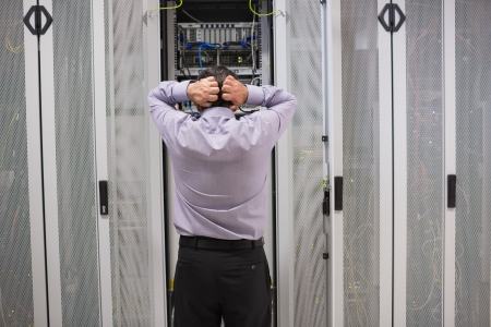 Technician getting stressed over server maintenance at server tower in data center photo