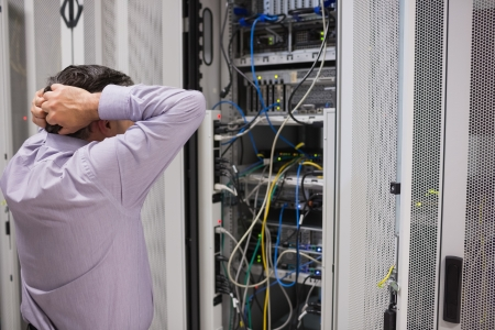 Technician feeling frustrated over server maintenance in data center photo