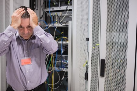 Man looking weary of data servers in data center photo