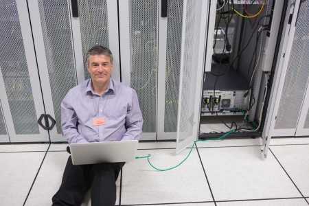 Smiling man doing server maintenance with laptop sitting on floor of data center photo