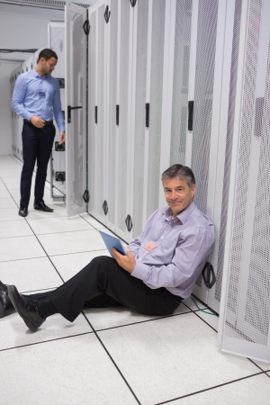 Smiling technician using tablet pc for server maintenance sitting on floor of data center photo