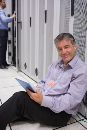 Smiling man sitting on the floor with his tablet and doing maintenance beside servers in data center photo