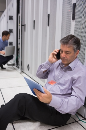 Technician on the phone doing server maintenance with tablet pc in server halllway of data center photo