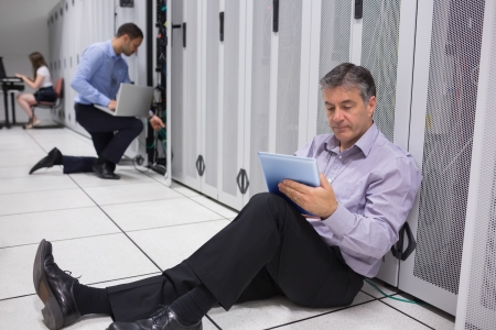 Various technicians working on data servers in data center with laptops and tablet pc photo