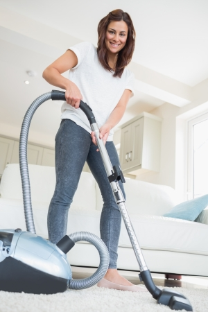 vacuum: Woman holding vacuum cleaner smiling at home  Stock Photo