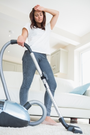 Tired woman with vacuum cleaner at home  photo