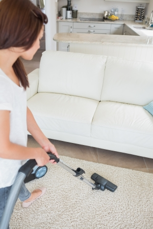 carpet clean: Woman cleaning the carpet with a vacuum cleaner Stock Photo