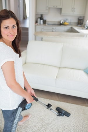Smiling woman hoover the rug in living room at home photo