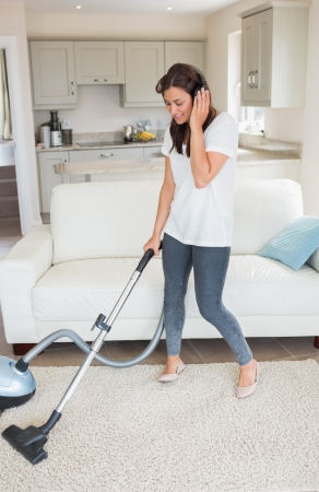 Woman standing holding a vacuum cleaner while wearing headphones  in the living room at home photo
