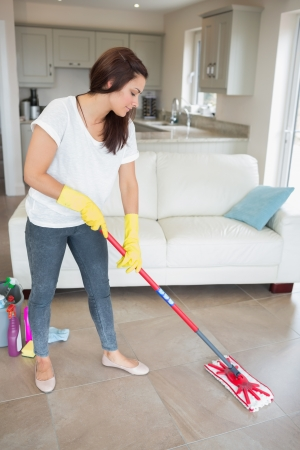 Woman mopping the living room floor of her home photo