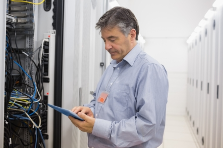 Technician using a tablet pc to check the server in data center photo
