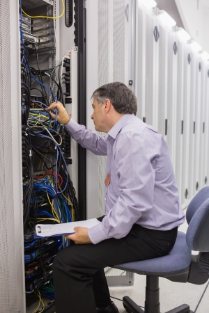 Technician with a clipboard checking servers in data center photo