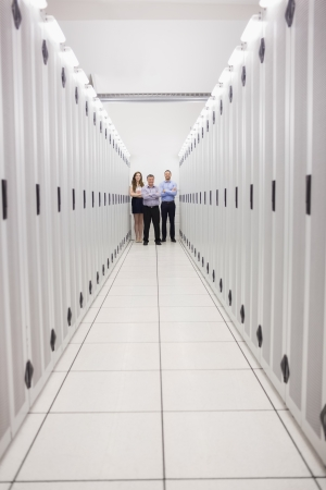 Technicians standing at end of server corridor in data center photo