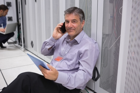 Technician phoning while working with his digital tablet and sitting on floor of data server photo