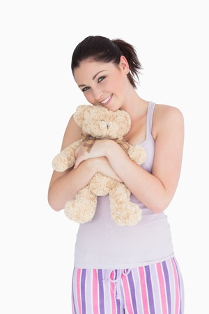Smiling woman holding a teddy bear against white background photo