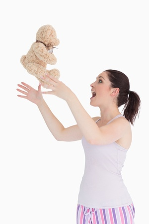Woman throwing her teddy bear in the air against white background photo