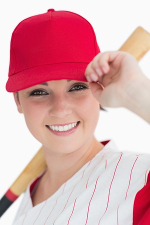 Woman holding a baseball bat and her cap against white background photo