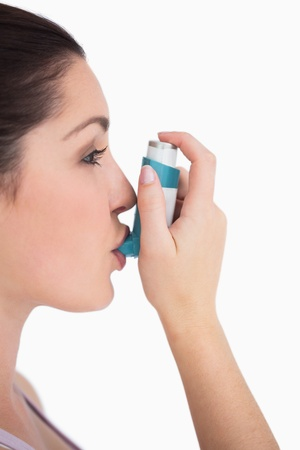 Woman using asthman inhaler against white background photo