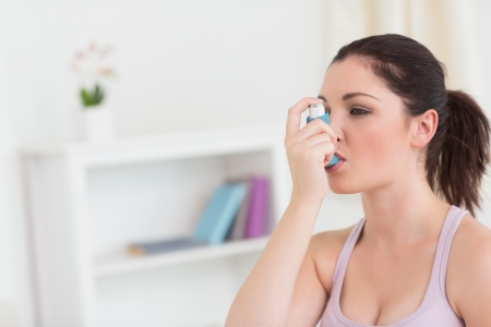 Brunette woman using asthma inhaler in living room photo